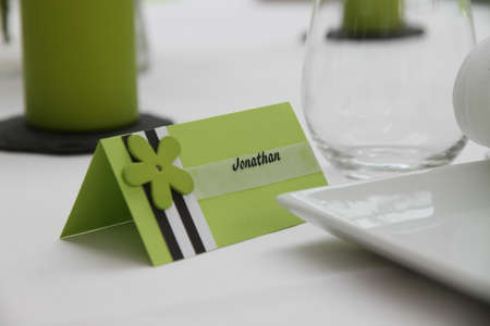 wedding table setting: Table detail in high key with a place card, plate, glass, napkin and candle Stock Photo