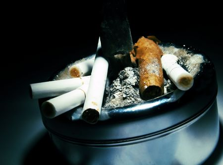 Ashtray full of cigarette butts and a cigar