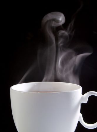 soothe: Cup of coffee with smoke on a dark background Stock Photo