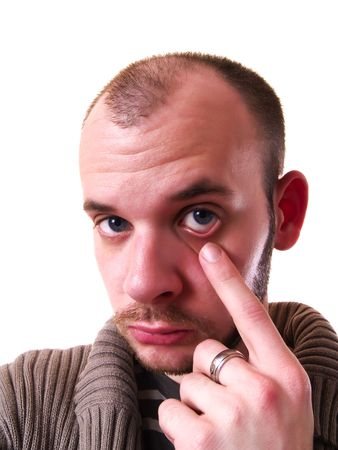 Close-up of an amazed young adult pointing a finger to his eye photo