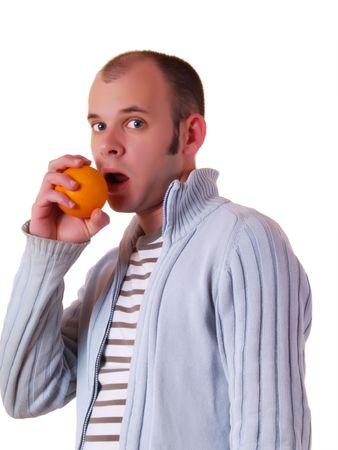 Young amazed man eating an orange photo