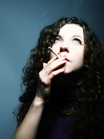 A portrait about a pretty lady with white skin and long brown wavy hair who is smoking photo