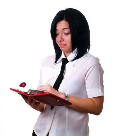 A portrait about a young attractive businesswoman with black hair who is holding a red calendar, she is sad because her agenda is full. She is wearing a white shirt and a black tie. photo
