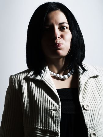 A high-key portrait about an attractive lady with black hair who is looking ahead, she is bulging out her cheeks and she is pouting. She is wearing a white coat, a black dress, and a white necklace. photo