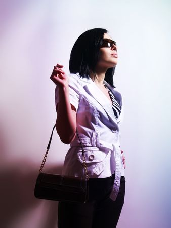 highkey: A high-key portrait about an attractive trendy girl with black hair who has a glamorous look. She is lighted colorful and brightly. She is wearing sunglasses, black pants, a white coat and a stylish handbag.