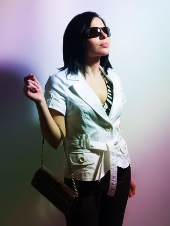 highkey: A high-key portrait about a pretty trendy lady with black hair who has a glamorous look. She is lighted colorful and brightly. She is wearing sunglasses, black pants, a white coat and a stylish handbag.