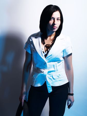 look for: A high-key portrait about a cute stylish lady with black hair who is lighted with blue, she is going for a holiday and she has an charming look. She is wearing black pants, a white coat and a stylish handbag. Stock Photo