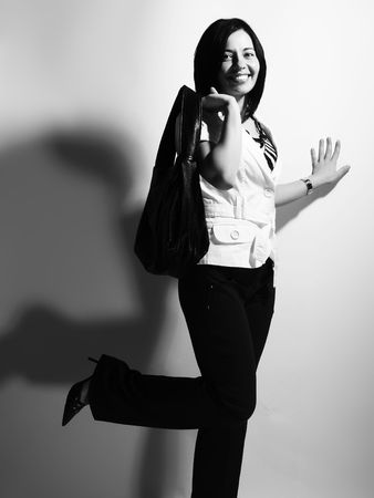 highkey: A black and white high-key portrait about a beautiful trendy girl with black hair who is smiling, she is having fun and she has an charming look. She is wearing black pants, a white coat and a stylish handbag.