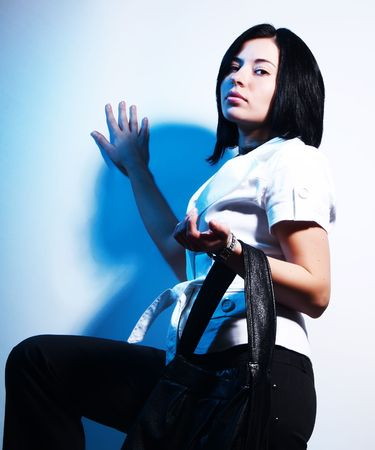 A high-key portrait about a cute trendy lady with black hair who is leaning against the wall, she is lifting up her leg and she has a glamorous look. She is wearing black pants, a white coat and a stylish handbag. photo