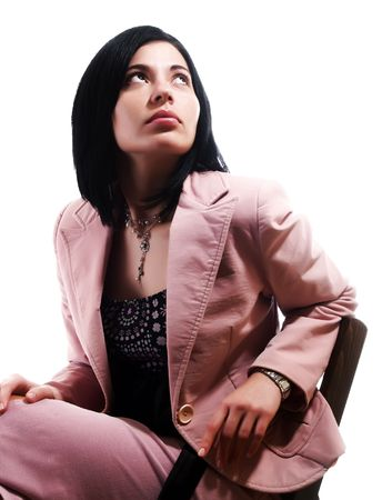 admiring: A portrait about an elegant trendy woman with black hair who is sitting on a chair, she is looking up and she is dreaming something. She is wearing a nice dress, a pink skirt and a pink stylish coat. Stock Photo
