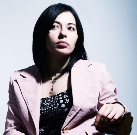 lost in thought: A portrait about an elegant trendy woman with black hair who is sitting on a chair, she is looking up and she is thinking. She is wearing a nice dress, a stylish necklace and a pink coat.