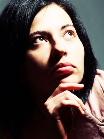 A closeup high-key portrait about an elegant trendy woman\ with black hair who is looking up and she is admiring something.\ She is wearing a stylish pink coat.