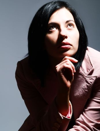 A closeup high-key portrait about a beautiful trendy lady with black hair who is looking up and she is dreaming. She is wearing a stylish pink coat. Stock Photo - 3063713
