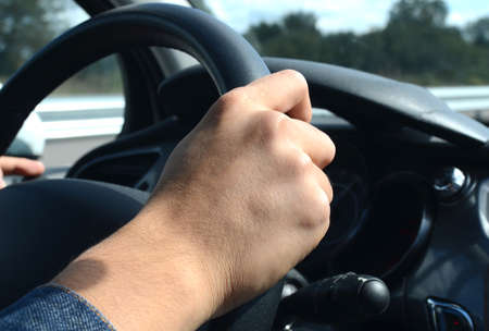 truck driver: Right hand holding the wheel while driving on road Stock Photo