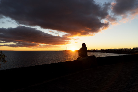 islas: Sunset in Playa Blanca as seen from the Boulevard with the lighthouse Pechiguera in the distance. Stock Photo