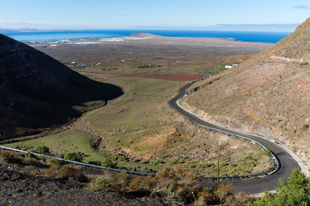 """From the so-called """"Mirador de Femes"""", 450 meters above sea level, visitors have a lovely view overlooking the """"Rubicon Lowlands"""" towards Playa Blanca with the """"Montana Roja"""" the Red Mountain and the southern tip of the island up to the neighbor island of"""