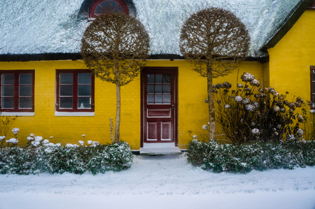 a house with a straw: Yellow house with straw roofing and some fresh snow, perfect Editorial
