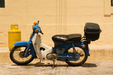 moped: Blue moped parked in front of a yellow gas bottle