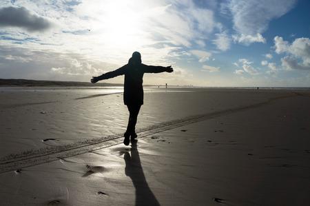 ijmuiden: Woman running towards the sun at the beach of IJmuiden