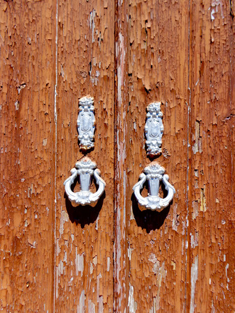 portugese: weathered door with door knockers in a typical Portugese house in Tavira, Portugal