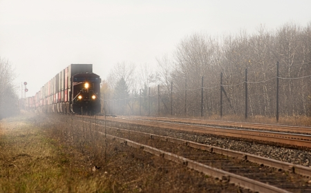 goods train: Freight train approaching on a railroad track through the mist  Stock Photo