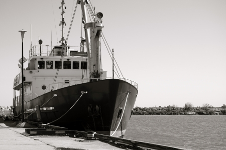 guard ship: Black and white image of a small research vessel anchored at the pier  Stock Photo