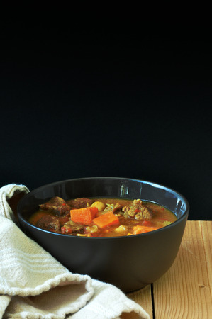 stew: Bowl of stew against a dark background
