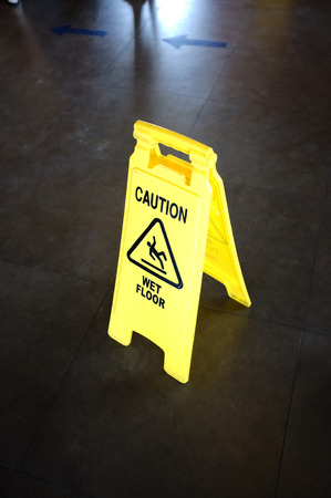 be wet: Caution yellow sign for wet floor warning on a floor Stock Photo
