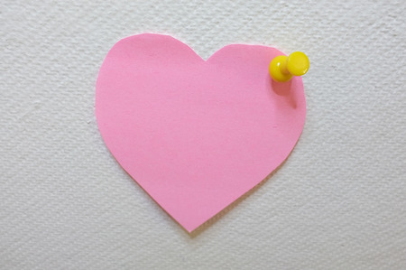 posted: Note paper in heart shape with yellow pin posted on white cork board background