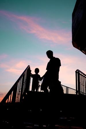 down the stairs: Hombre silueteado y el niño caminando por las escaleras en la puesta del sol Foto de archivo