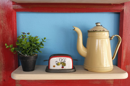 wooden shelf: Retro kitchenware and plant pot on wooden shelf, blue background with red frame Stock Photo