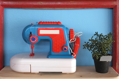 maquina de coser: Juguete y la m�quina de coser de la vendimia en fondo azul con el pote de la planta Foto de archivo