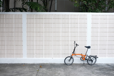 Orange bicycle parks in front of wall