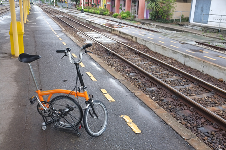 railroad station: Folding bicycle parked at railroad station after raining
