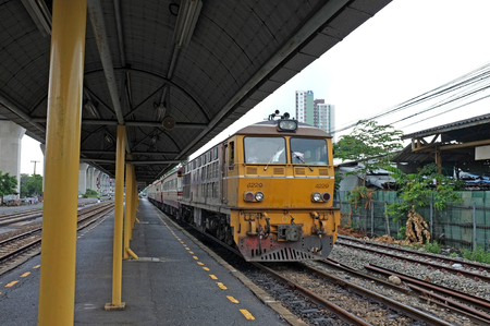 Railway station with yellow train arrival Editorial