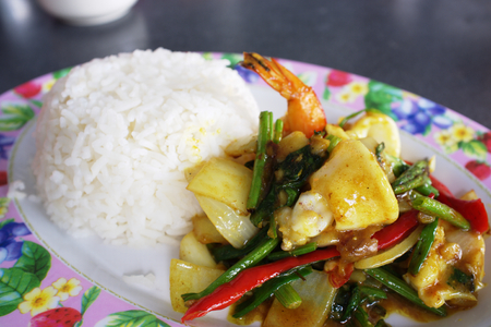 Seafood with Yellow curry sauce with rice , sauteed seafood contains shrimp squid,