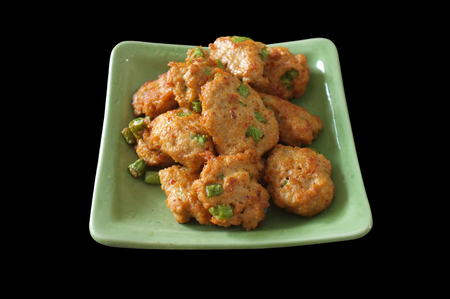 Fried Fish-paste balls / Fried fish cake / Tod Man Pla / Deep-fried curried fish patties in green white dish.