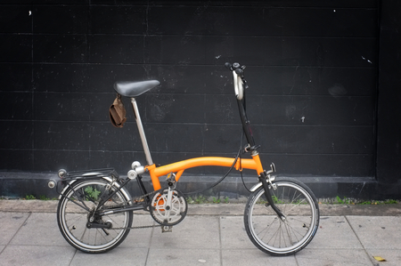 A Orange Brompton folding bicycle Standard-Bild