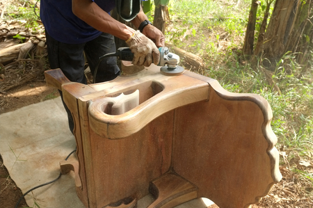lose up of a carpenter scrubbing wood chair with handheld electric scrubber. 版權商用圖片