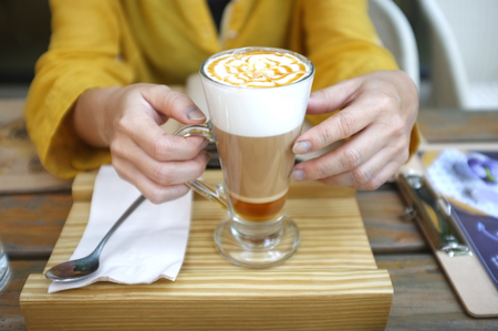 Woman hand hold cup of Caramel Macchiato , Concept CAFE 写真素材 - 124719043