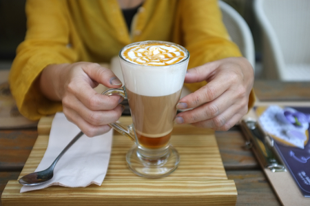 Woman hand hold cup of Caramel Macchiato , Concept CAFE 写真素材 - 124719044