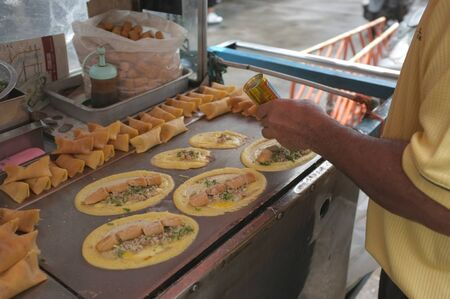 The man cooking Soft Waffle ,  Roll pancake stuffed with pork with custard and eeg ,Thai dessert. Stok Fotoğraf