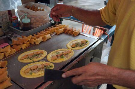 The man cooking Soft Waffle ,  Roll pancake stuffed with pork with custard and eeg ,Thai dessert. 写真素材