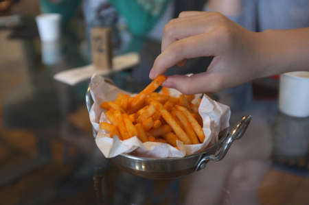 Hand holding French fries with chili cheese powder in a pan Stockfoto