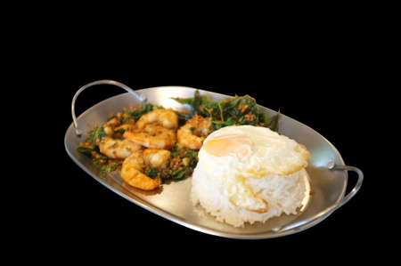 Stirred-fry shrimps or prawns with basil leaves, fried egg over rice. Thai food