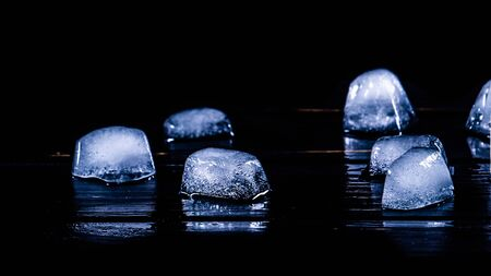 Blue Ice cubes on black table. Banque d'images - 131796474
