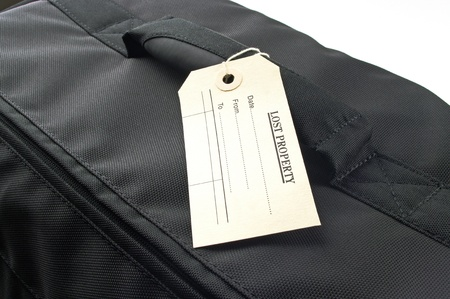 black travel bag and lost property tag