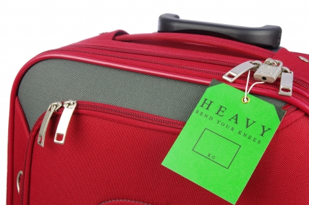 luggage tag: heavy warning label on a red travel bag