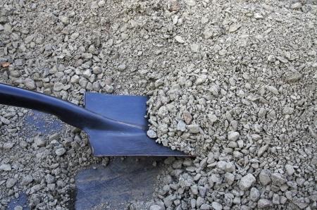 black shovel digging in grey gravel