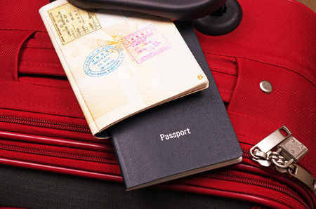 red suitcase and open passports  Stock Photo